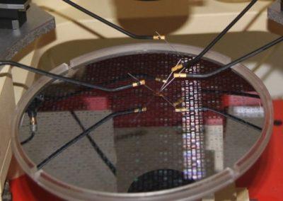 Una fetta di silicio aperta contenente vari MEMS in un banco punte con micromanipolatori